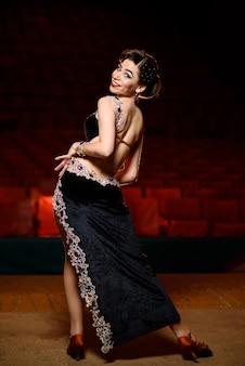 Красивая девушка в черном платье танцует на сцене