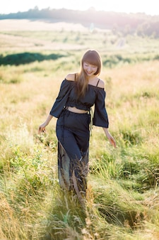 夏の日没時に牧草地で屋外を歩いて笑顔の黒いスーツの美しい少女