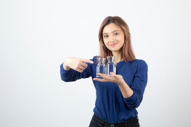 Красивая девушка в голубой блузке, держа стакан воды и указывая на него.