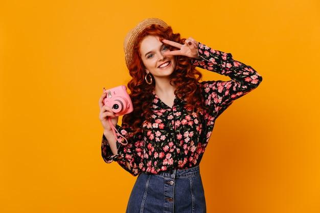 Красивая девушка в веселом настроении с белоснежной улыбкой показывает знак мира и делает фото на мини-камеру.