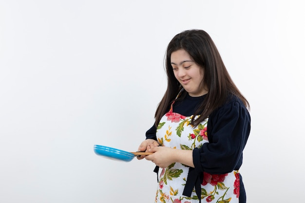 Красивая девушка в красочном фартуке готовится к приготовлению с ложкой и сковородой.