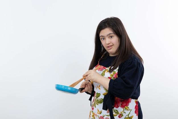 숟가락과 팬으로 요리를 위해 준비하는 다채로운 앞치마에서 아름 다운 소녀.