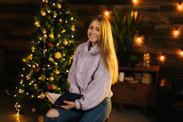 クリスマスツリーとお祝いの花輪の壁を背景に本を手にポーズをとる居心地の良いセーターの美しい少女。カメラを見ている素敵な女の子。