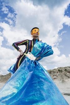 Красивая девушка в креативном праздничном наряде, желтой пластиковой маске и синем блестящем снуде