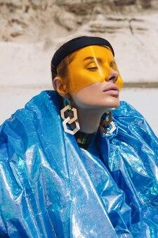 창의적인 축제 복장, 노란색 플라스틱 마스크 및 파란색 반짝이는 목줄의 아름다운 소녀
