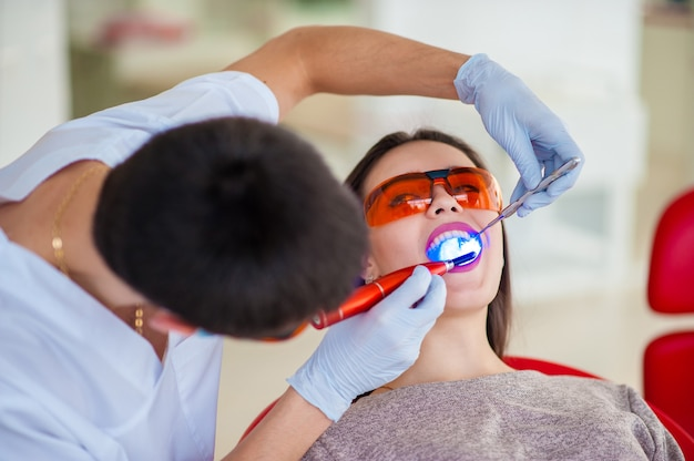 Красивая девушка в стоматологии лечит зубы