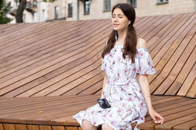 電話でヘッドフォンで音楽を聴いて、屋外のベンチに座っているドレスの美しい少女