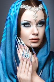 長い爪と明るい青色のメイクで東アラビアのイメージの美しい少女。灰色の背景にスタジオで撮影した写真