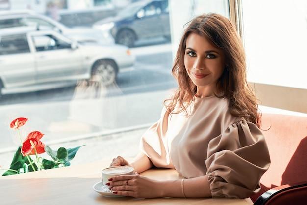 Красивая девушка в элегантном платье и очаровательной улыбке позирует фотографу в городе