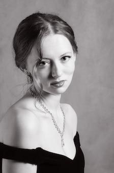 ネックラインのイブニングドレスの美しい少女。レトロなスタイルの黒と白の肖像画