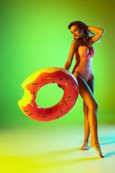 ネオンの光の夏のグラデーションスタジオの背景に分離されたファッショナブルな水着の美しい少女