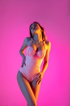 Красивая девушка в модном купальнике, изолированном на фоне студии градиента в неоновом свете.