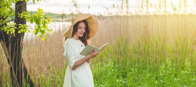 책을 읽고 필드에서 아름 다운 소녀입니다. 소녀는 잔디에 앉아 책을 읽고. 휴식과 독서