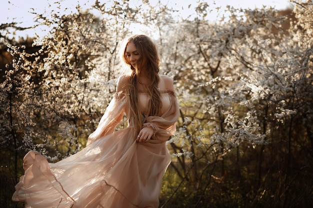 花盛りの木で美しい少女。庭のチュールのパウダードレスの女性。素敵でかわいい女の子