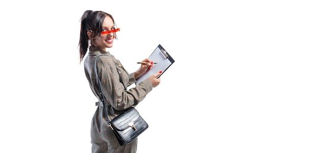 Красивая девушка в очках составляет список покупок.