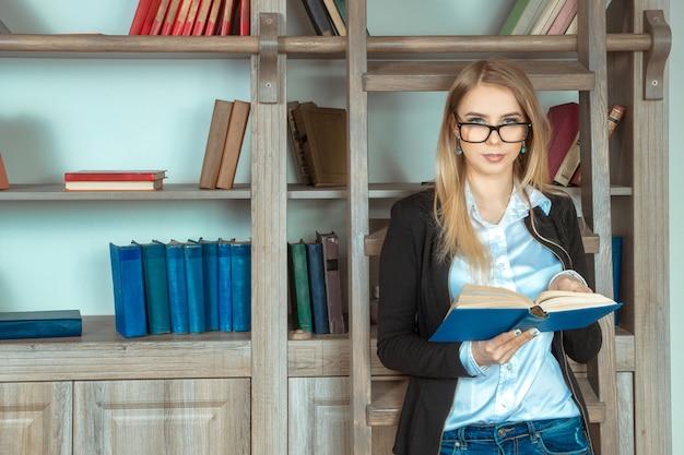 本の大きな棚と本を手に持って木製の階段の近くに立っている眼鏡の美しい少女