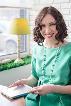 テーブルに座って、白いレンガの壁と窓の背景に日光の下でタブレットを見て緑のドレスの美しい少女