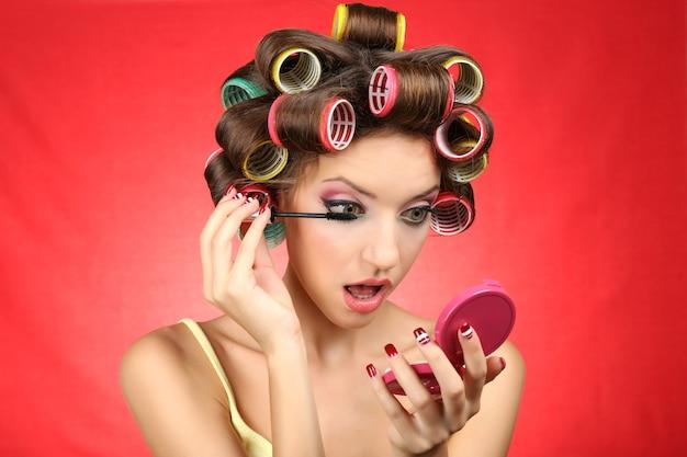 Красивая девушка в бигуди на красном фоне