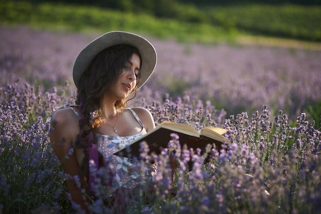 紫色のラベンダー畑に座って本を読む帽子の美しい少女。