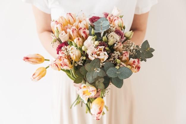 Красивая девушка держит в руках букет цветов на белой стене