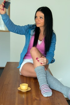 自宅の服で美しい少女は、スマートフォンを使用して台所に座っている間笑顔