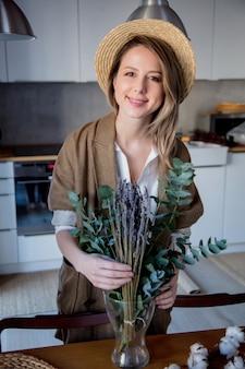 집에서 부엌에서 유칼립투스와 목화 식물 재킷에 아름 다운 소녀. 라이프 스타일의 건강과 생태 개념