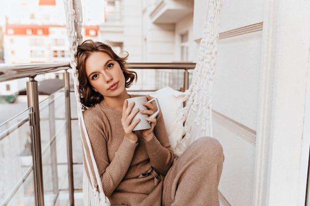 朝のコーヒーを飲むニットドレスの美しい少女。バルコニーでお茶を保持しているロマンチックな白人の若い女性。