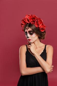 Красивая девушка в одежде la muerta и черепа составляют, глядя в камеру во время хэллоуина, закрывают глаза