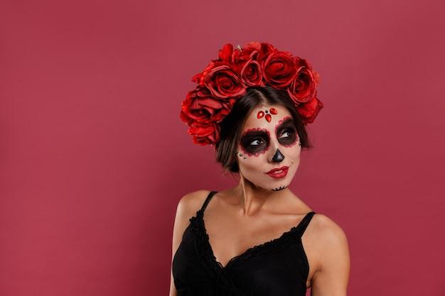 Красивая девушка в одежде la muerta и черепа макияж смотрит в камеру во время хэллоуина
