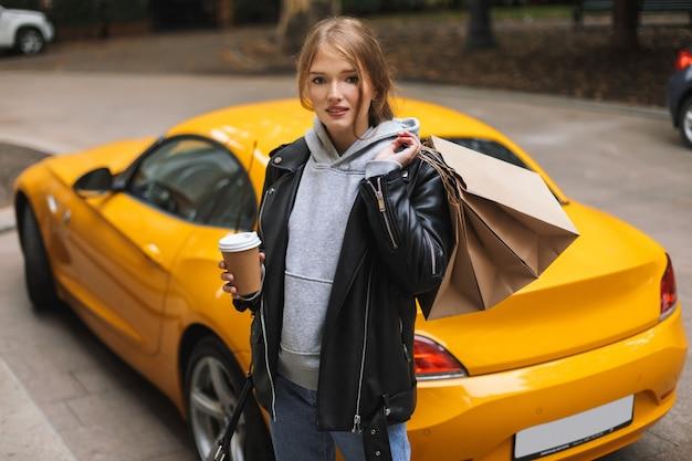 夢のようにしながら行くコーヒーと買い物袋を手に持っている革のジャケットの美しい少女