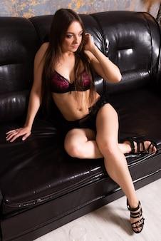검은 가죽 소파에 앉아 란제리에서 아름 다운 소녀. 어떤 목적을 위해.