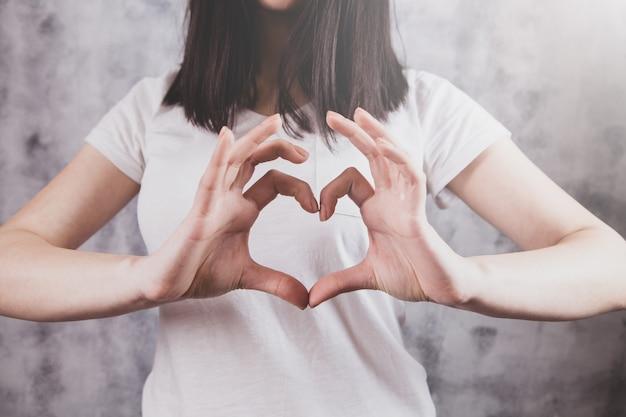 Красивая девушка делает сердечный жест руками