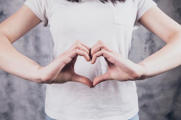 Красивая девушка делает сердечный жест руками Premium Фотографии