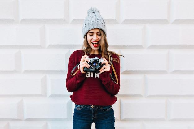 Красивая девушка в свитере марсала на серой стене. она носит вязаную шапку, с удивлением смотрит в камеру в руках.