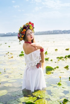 호수에 서있는 국가 옷에서 아름 다운 소녀