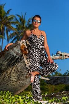 Красивая девушка в комбинезоне и солнцезащитных очках позирует на пляже с высокими пальмами и белым песком возле рыбацкой лодки. африка момбаса побережье индийского океана