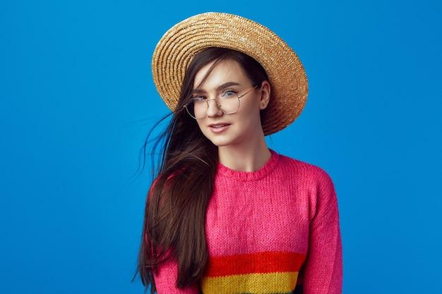 Красивая девушка в очках радужного свитера и соломенной шляпе позирует очаровательно