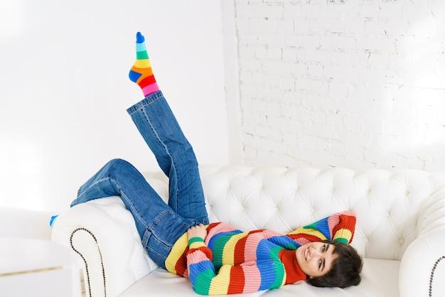 虹色のセーターを着た美少女が白いソファに横になり、白人のかわいい若い女性に微笑む...