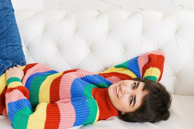 レインボーセーターの美しい女の子は白いソファと笑顔に横たわっています