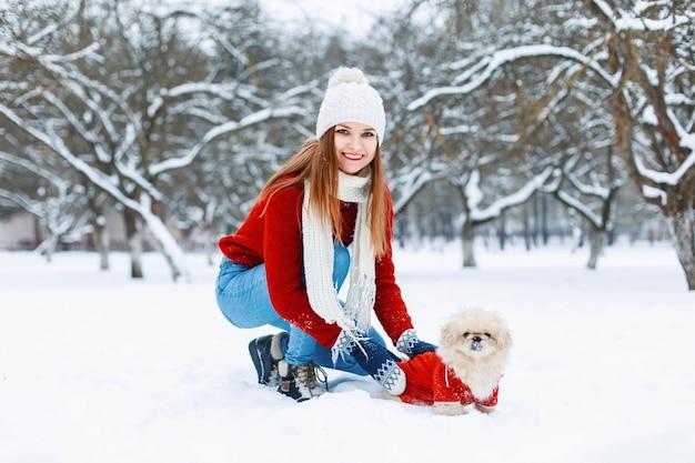 犬の散歩赤いニットセーターの美しい少女