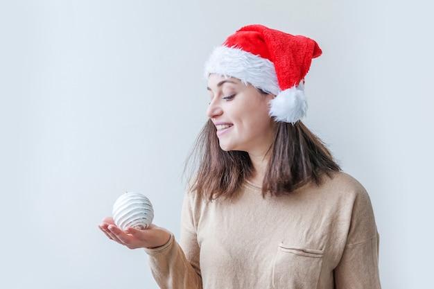 흰색 배경에 고립 된 손에 크리스마스 트리 장식 공을 들고 빨간 산타 클로스 모자에 아름 다운 소녀. 젊은 여자 초상화, 진정한 감정입니다. 행복 한 크리스마스와 새 해 휴일 개념입니다.