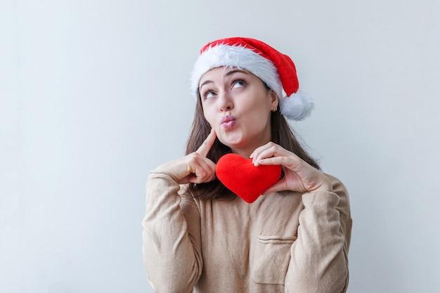 白い背景で隔離の手に赤いハートを保持している赤いサンタクロース帽子の美しい少女