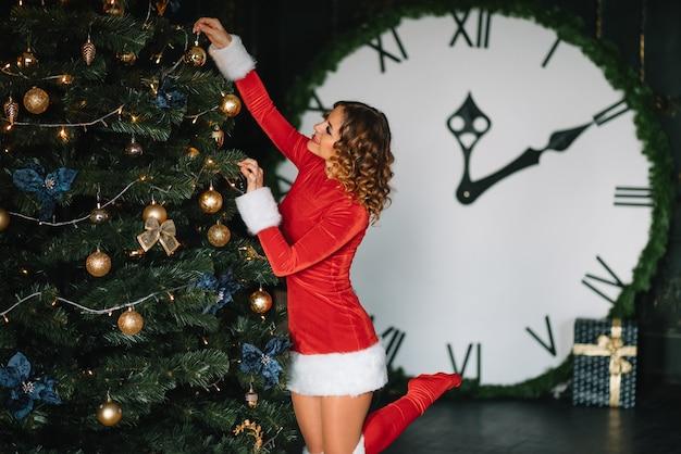 暖炉とクリスマスツリーの近くに赤いサンタスーツの美しい少女。豪華なアパートメントでの魔法のクリスマスナイトは、クリスマスライトを飾りました。