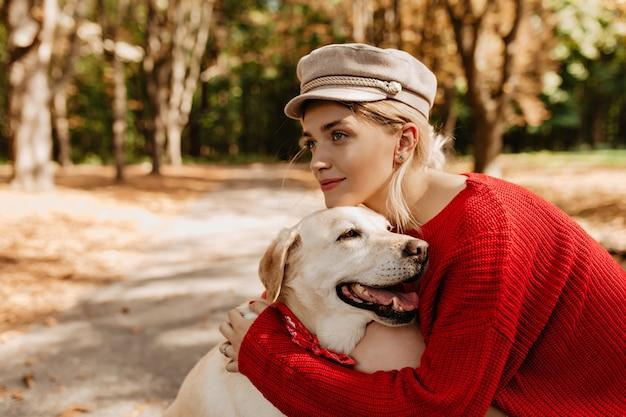 빨간 스웨터 사랑스러운 아름다운 소녀는 공원에서 그녀의 사랑스러운 래브라도를 잡아. 강아지와 함께 가을에 야외 좋은 시간을 보내고 꽤 금발 여자.
