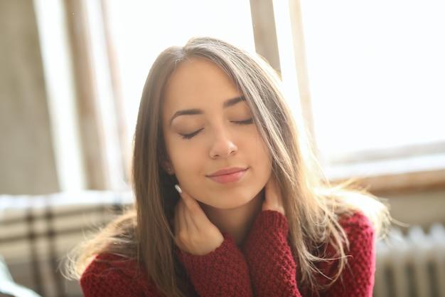 赤いセーターで美しい少女