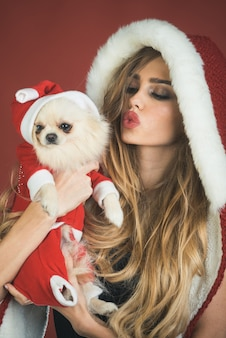 Красивая девушка в шляпе санта-клауса с домашним животным рождество, новый год, зимнее счастье концепция улыбающаяся женщина