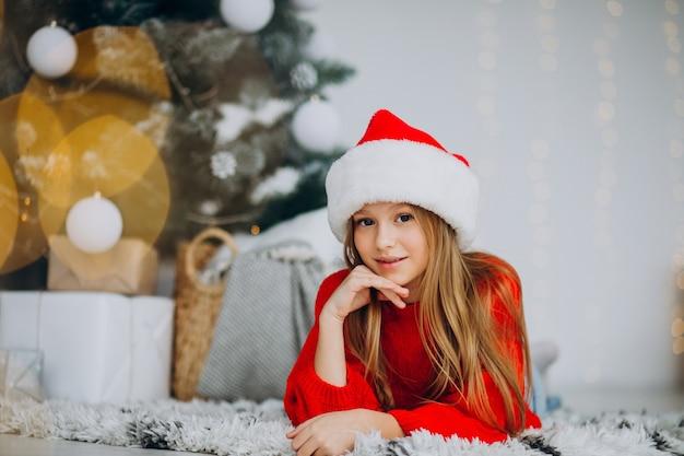 クリスマスツリーの下でサンタの帽子の美しい少女