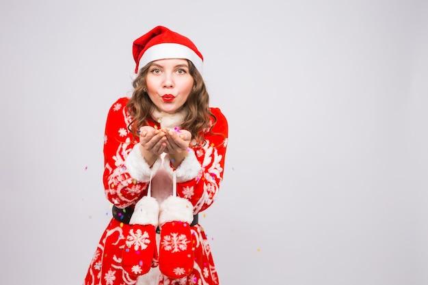 Красивая девушка в костюме санта-клауса встречает новый год 2019, дует конфетти на камеру