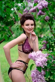 Красивая девушка в сексуальном нижнем белье позирует на природе