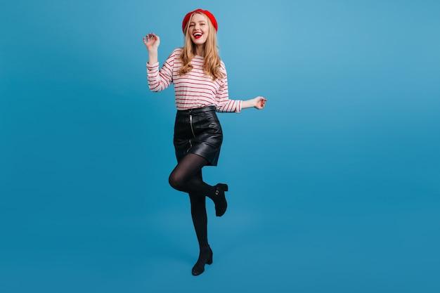 Красивая девушка в короткой юбке танцует на синей стене. взволнованная хорошо одетая женщина, выражающая счастье.